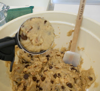 Scooping the chocolate chip cookie batter.