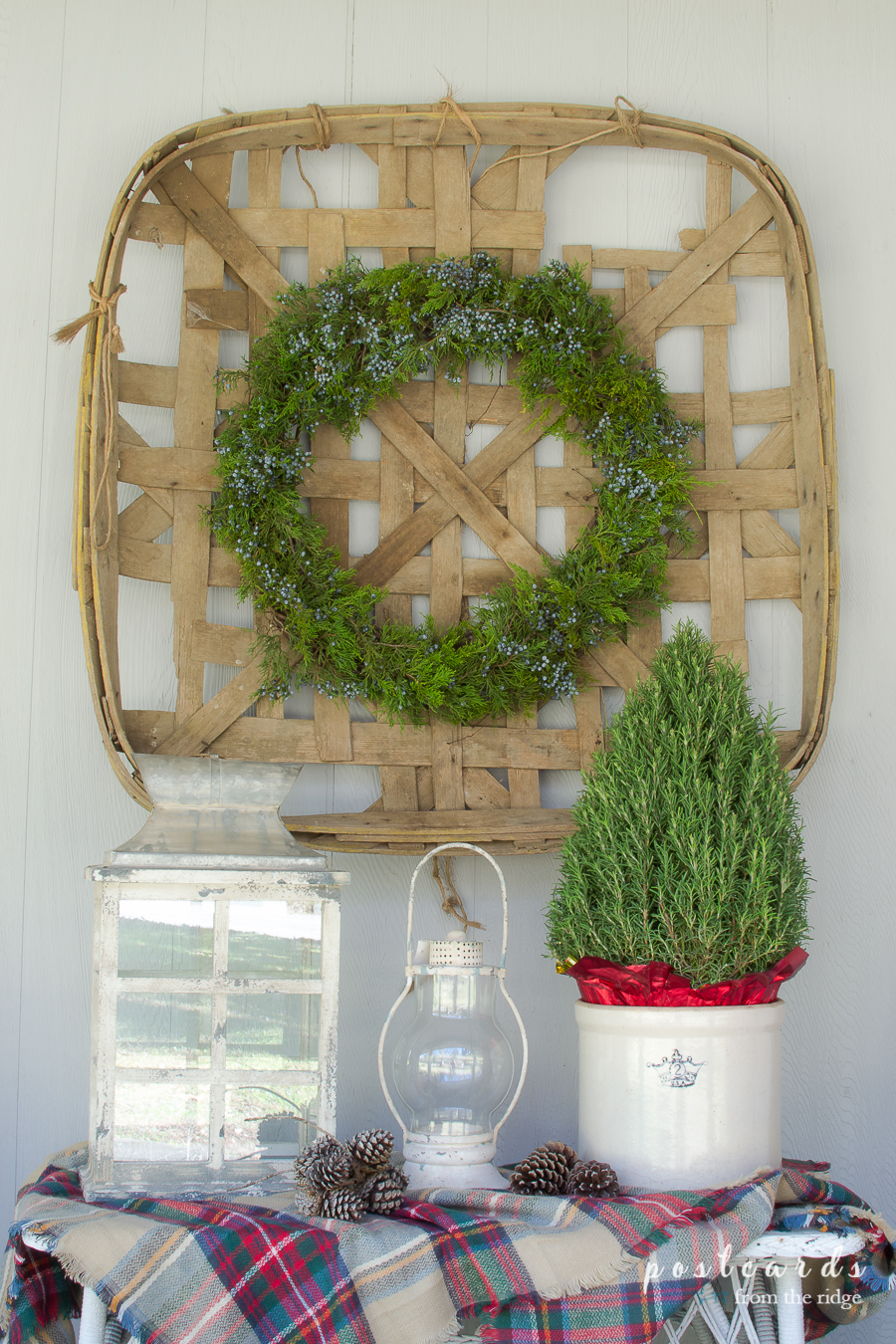 vintage tobacco basket with fresh wreath and candle lanterns for Christmas porch decor