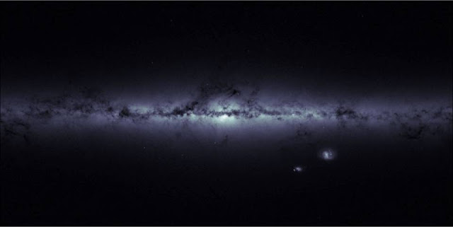 An international team of astrophysicists has identified a link between dark matter and the oldest stars in our galaxy, the Milky Way. This image of the Milky Way (and its neighboring Magellanic Clouds) is not a photograph but a visual representation of the locations of stars detected by ESA's Gaia satellite. Brighter regions indicate higher concentrations of stars. The plane of the Milky Way, where most of the galaxy's stars reside, runs horizontally across the center. Darker regions across this broad strip of stars correspond to dense, interstellar clouds of gas and dust that absorb starlight along the line of sight. (Image courtesy of ESA/Gaia – CC BY-SA 3.0 IGO)