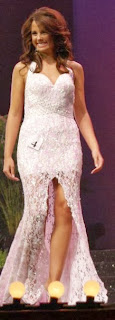 A smiling brunette fashion model in a form-fitting white dress with a lace pattern.