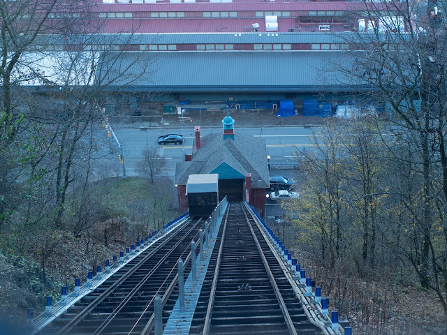 A view looking down an incline with tracks for cars, passing through trees and up to a red building on a two-line road with large buildings on the opposite side.