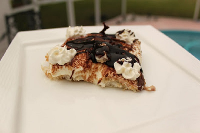 This is a slice of tiramisu that has a no bake eggless filling with hot fudge on top, frangelico and coffee mixture, sponge cake, angel food cake and whipped cream with unsweetened cocoa powder for garnish