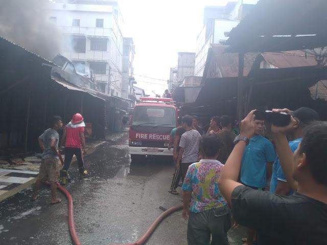 Warga menyaksikan petugas pemadam kebakaran yang berusaha memadamkan api yang membakar rumah di Jalan Cipto Kisaran