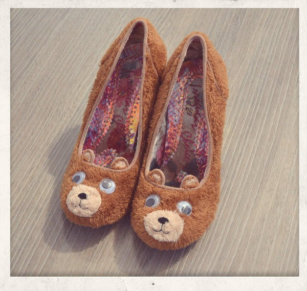 pair of brown furry bear shoes with googly eyes sitting side by side on floor