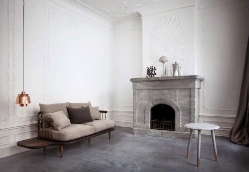 in einem Raum steht ein Sofa aus Holz und Stoff, an der Decke hängt eine kupferfarbene Lampe