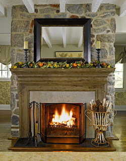 warm stoned fireplace design with cream rug on laminate floor plus candles decorations
