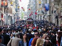 İstanbul İstiklal Caddesindeki kalabalık insan topluluğu ve aralarından geçen tarihi tramvay