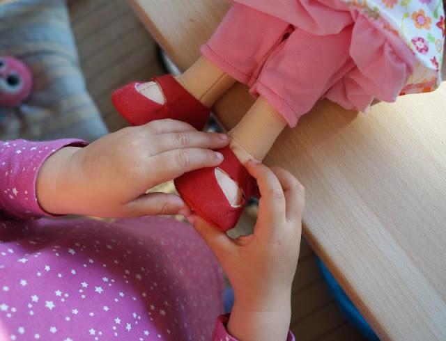 Puppen sind unglaublich wichtig für Kinder, als Freunde und Begleiter der Kindheit. Ich stelle Euch die wunderschön gestalteten und kuschelweichen Puppen Milla und Matze von HABA vor, die gerade bei uns eingezogen sind. Hier: Mädchenpuppe Milla beim Schuhe anziehen.