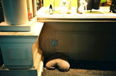 Reto 5 líneas de Adella Brac (Dic. 2017). En imagen una almohada en el suelo frente al aparador de una tienda.