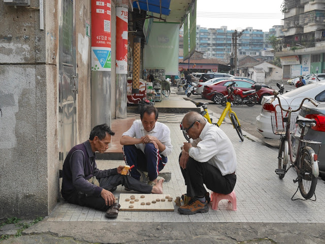 man holding cigarettes and a man with a tobacco pipe playing a game of xiangqi