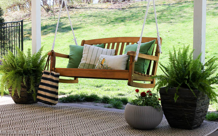 Spring covered patio refresh with porch swing, outdoor rug and potted ferns