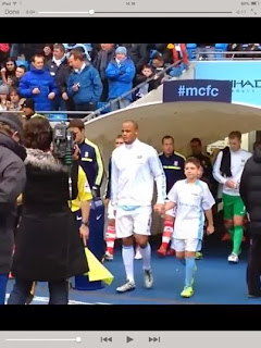 A young mascot with Vincent Kompany