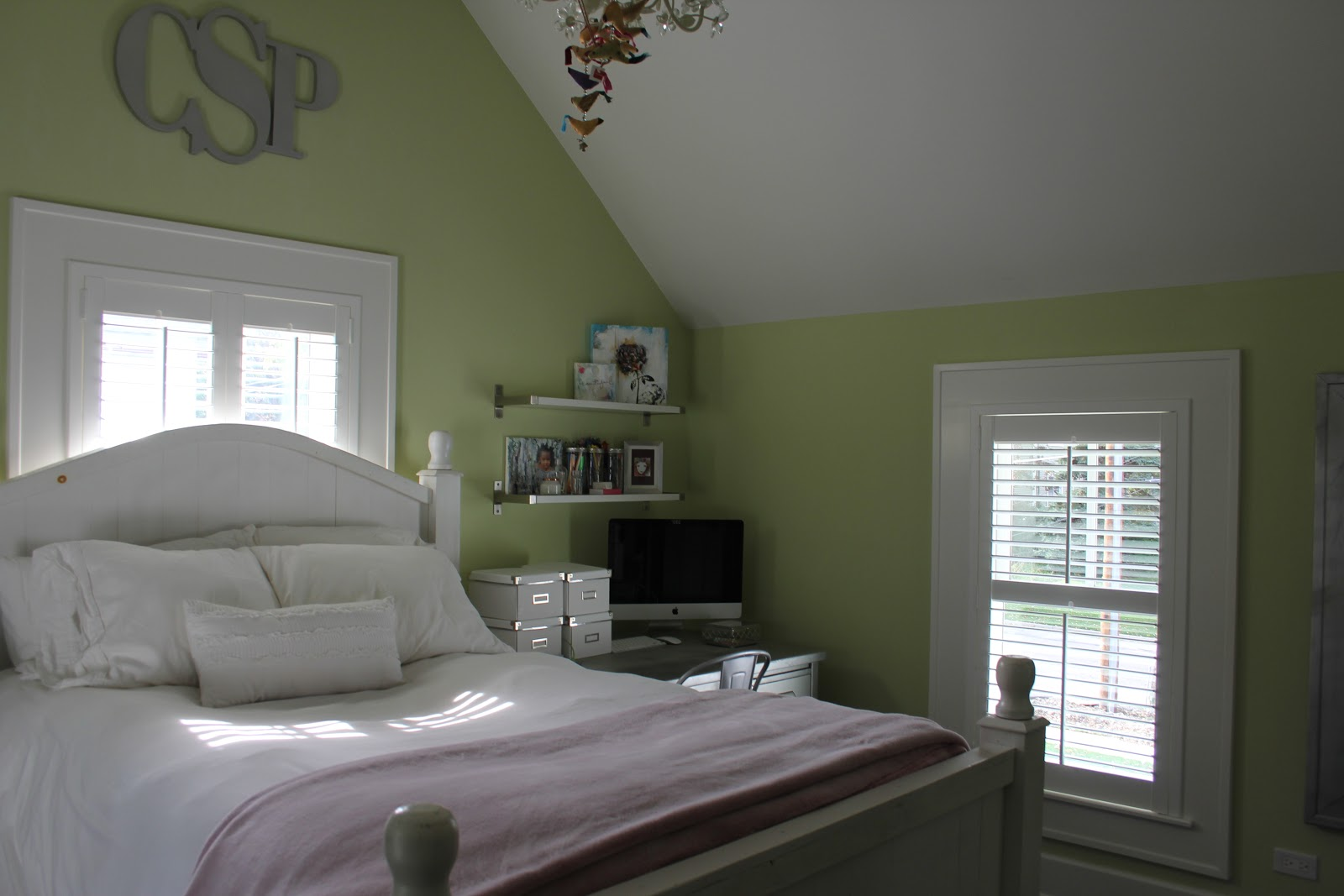 Modern farmhouse bedroom with green walls and plantation shutters on Hello Lovely Studio