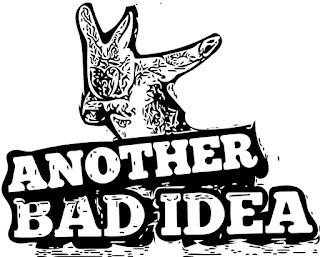 Logo another bad idea graphic black and white text a cartoon bunny in the back round head down with arm to face pushing away the hate with the other