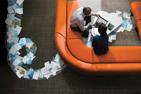 Overhead view of business man and business woman sitting on couch with HP Notebook and HP iPAQ Handheld with information moving around them