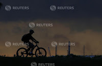 A man cycles past a chimney giving off emissions in an industrial area of Singapore, Jan. 5, 2016. (Credit: Reuters/Tim Wimborne) Click to Enlarge.
