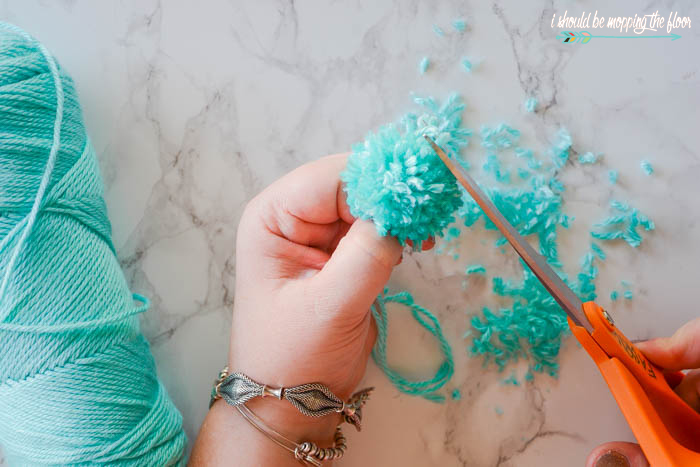 How to make yarn pom poms using a fork and clothespin. This easy method doesn't require any special tools (or cutting off the circulation in your hand making poms the old fashioned way!).