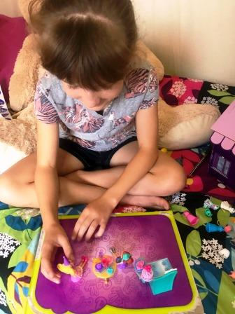 Girl playing with Polly Pocket Birthday Party set