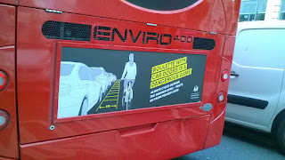 Advert on back of London bus warning cyclist to ride at least 1m from parked cars to avoid being doored.