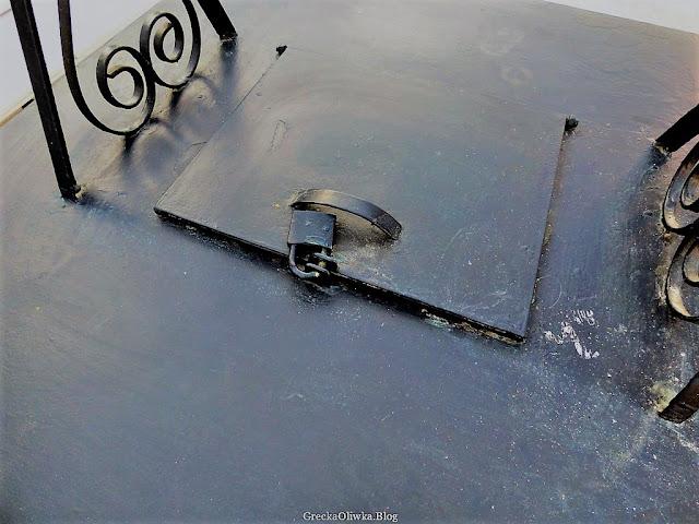 kłódka na czarnej metalowej osłonie studziennej w mieście Mykonos
