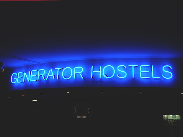 Blue neon sign reading Generator hostels