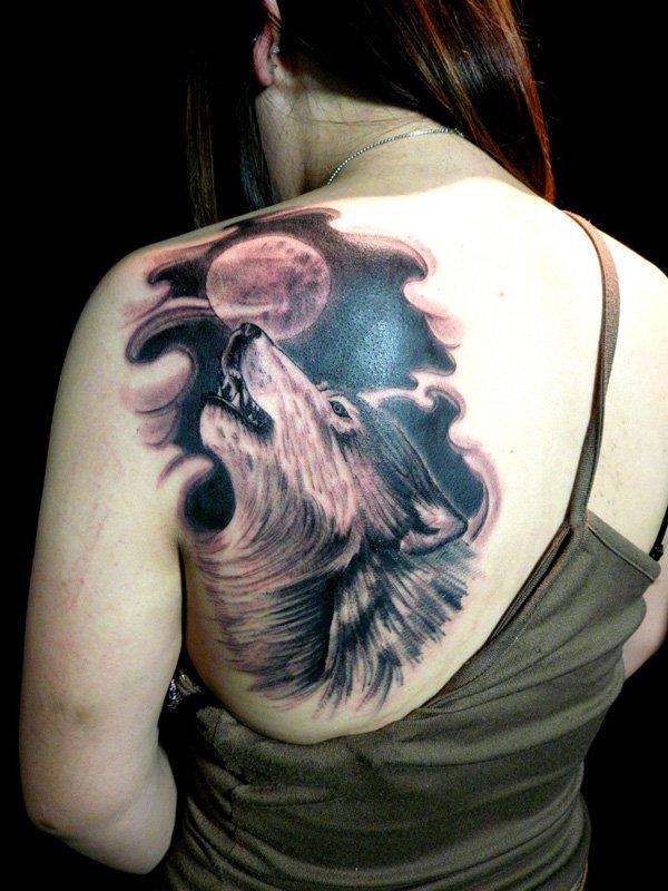 vemos el tatuaje de un lobo en la espalda de una chica morena con el pelo muy largo que se lo ha echado hacia un lado