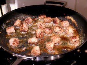 Swedish meat balls frying in a frying pan. Spaced in the pan so they do not steam.