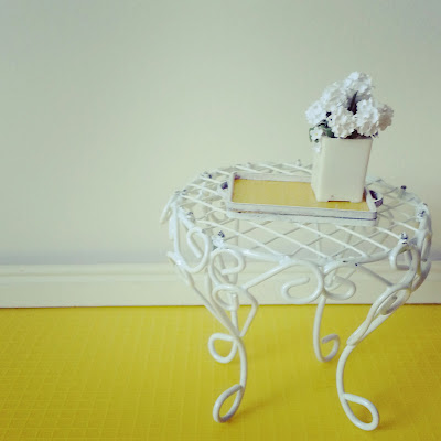 Modern one-twelfth scale white wire side table, holding a yellow and white tray with a white vase of daisies on it.