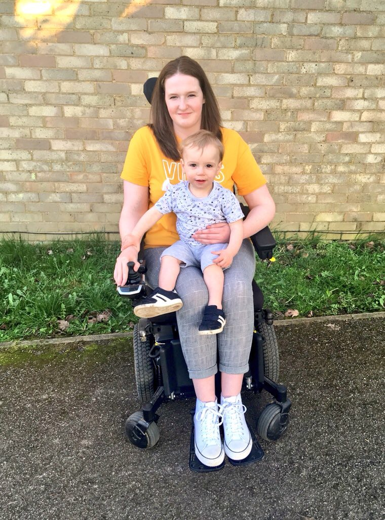 Shona is sitting in her powerchair wear a yellow top, grey checked leggings and white converse style shoes, she is smiling. Her 1 year old nephew is sitting on her lap with his hand rested on hers.