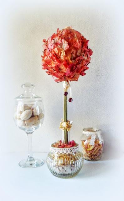 Arbol topiario junto a centro de mesa y frasco con pétalos de rosas secos