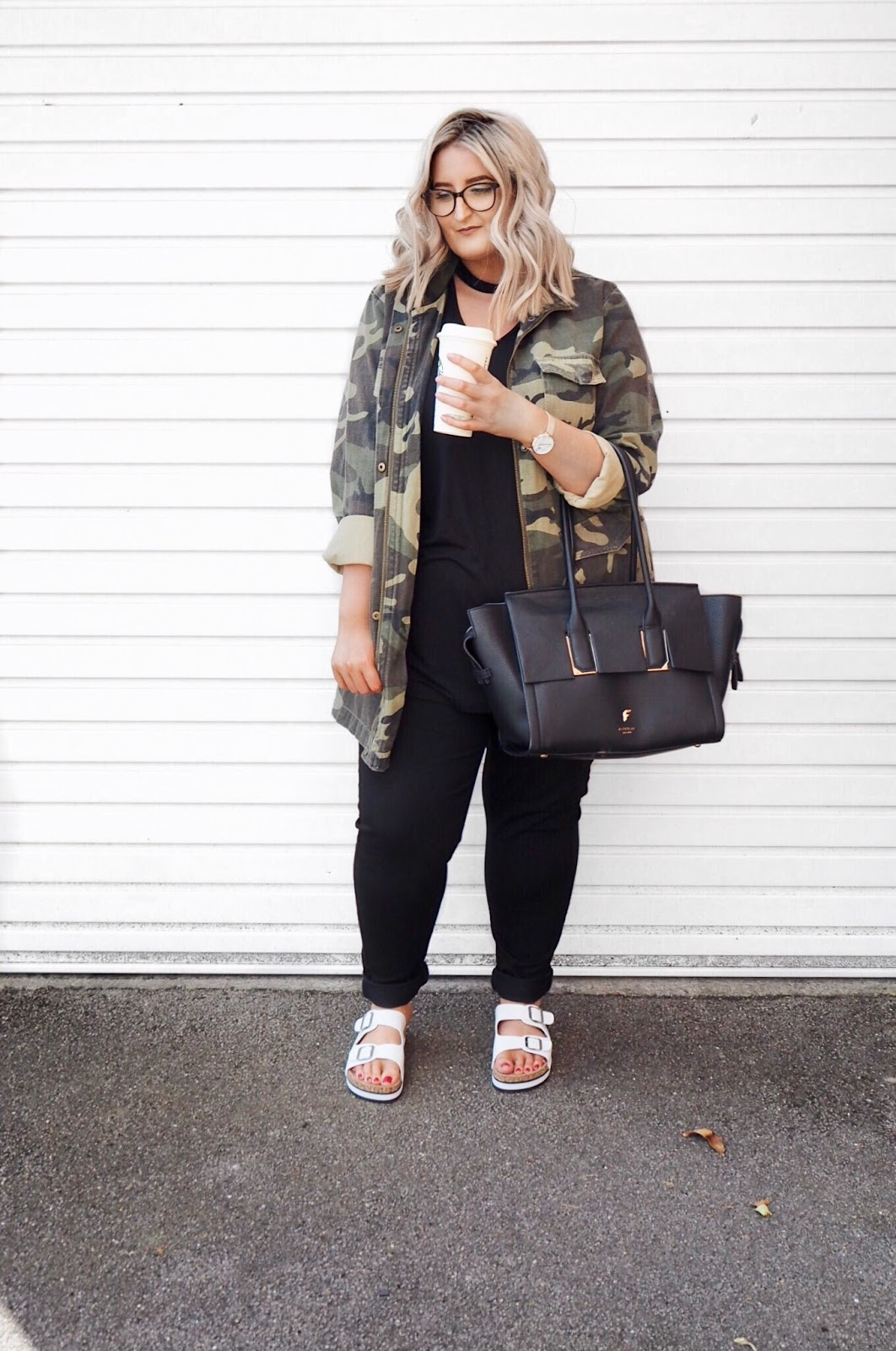 Plus size blogger wearing Yours Clothing camo jacket, choker top, black skinny jeans, white cork sandals, with a Starbucks and a handbag, against a white garage background