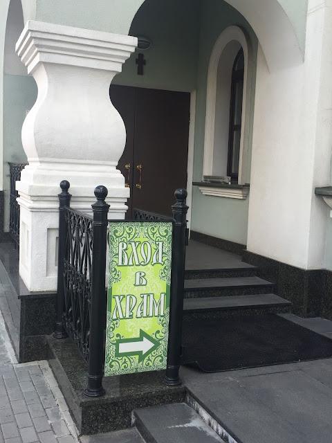 На фото - изображение плаката-указателя входа в храм