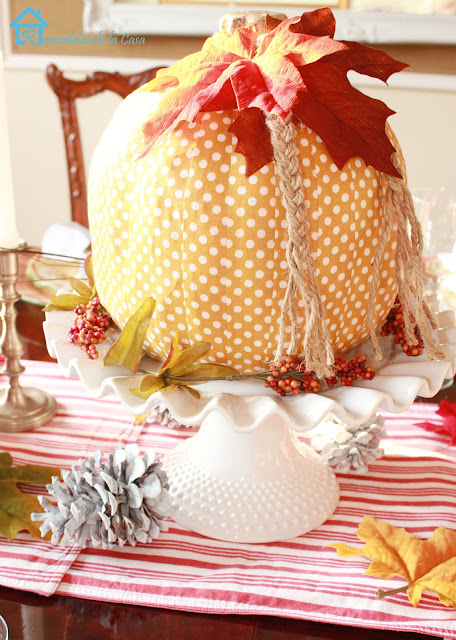 yellow polka dot pumpkin on white cake platter - pinecones and striped runner