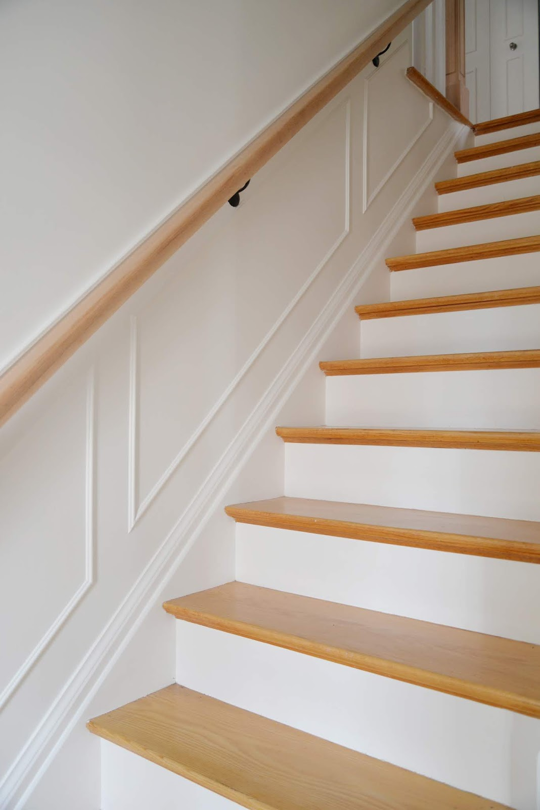 stairway with white walls, moulding, white risers and natural stair treads