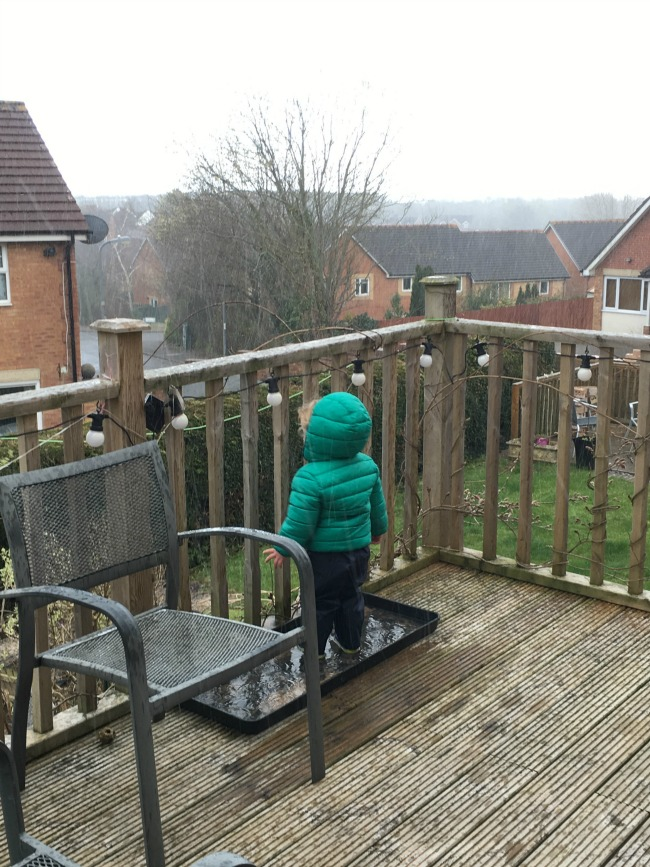 toddler in wellies and coat stood in tray full of water while it rains heavily