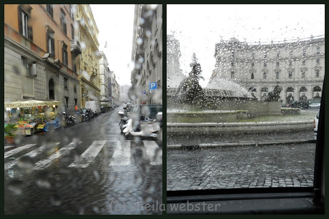 The rain spattered windows of the taxi cab blurred the view in Rome.