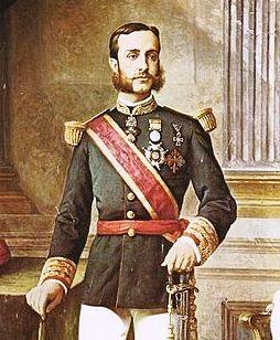 Reatro al óleo del joven rey, con barba y bigote, vestido con traje militar y medallas en el pecho.