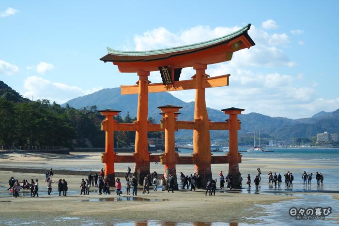 Torii à marée basse et foule à ses pieds, plage de Miyajima, Hiroshima-ken
