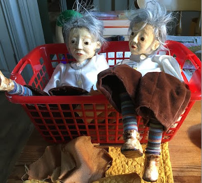 Two puppets by Corina Duyn lying in a basket waiting for their jackets to be sewn