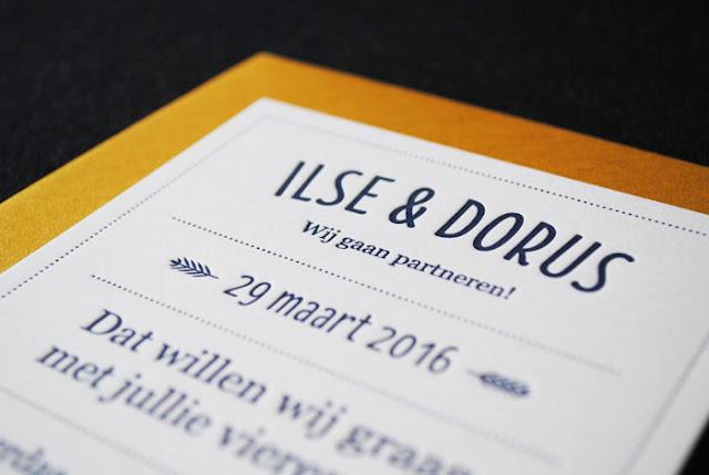 Close up van een diepdruk trouwkaartje met donkerblauwe inkt op een gouden envelop
