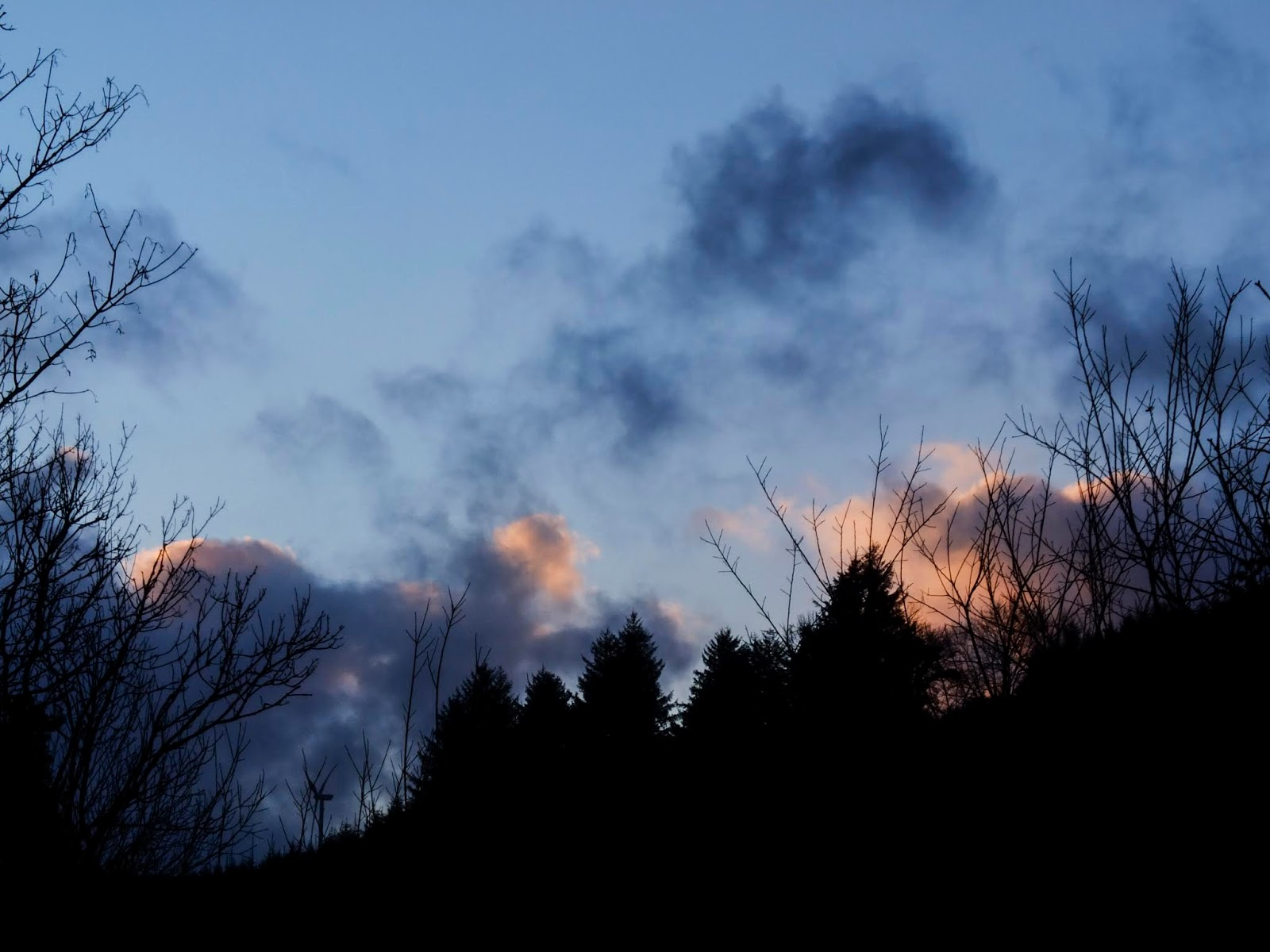 The last of sunset clouds going down behind the hillside in North Cork.