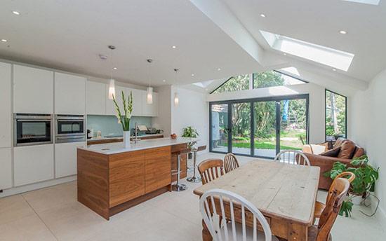 Phòng bếp màu trắng theo phong cách tối giản với đảo bếp gỗ ấm cúng và một chiếc bàn ăn bằng gỗ màu sáng.