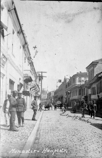 "The main street (Sirok Sokak) in front of hotel ""Bosna"" in 1916. German soldiers standing and posing for this photograph. In the background are seen Isak and Yeni Mosque. Telephone poles on left side of this photograph confirm that phones in the city were in use. Old houses on the right side of this image were ruined by bombing in 1917."