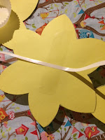 A string of ribbon being glued to the back of the daffodils
