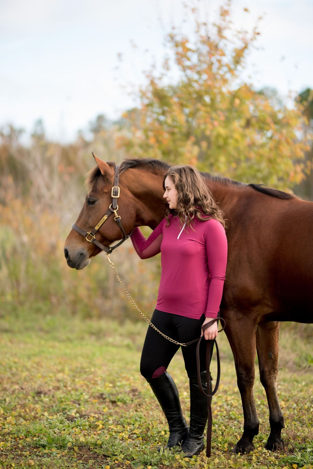 Brunette equestrian girl wearing Botori Life black and merlot riding pant with the tailored sportsman ice filled shirt in claret and ariat tall riding boots with brown bay quarterhorse
