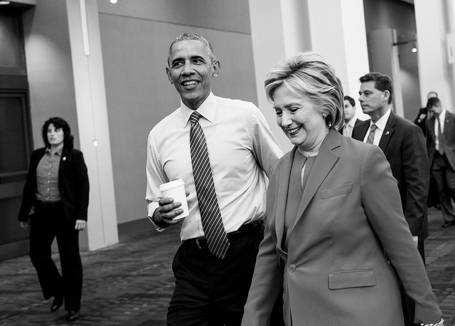 black and white image of President Obama, holding a cup of coffee, and Hillary Clinton walking down a hall before the event, chatting and smiling