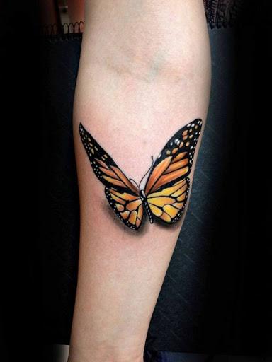 A laranja e a Borboleta Preta no Braço Inferior da Tatuagem