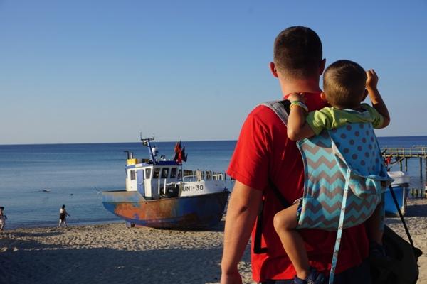 tata z synem w onbu nad morzem w porcie unieście