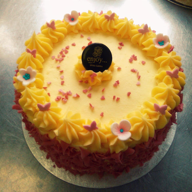 lemon butter cream cake with pink butterflies for decoration and little pink flowers