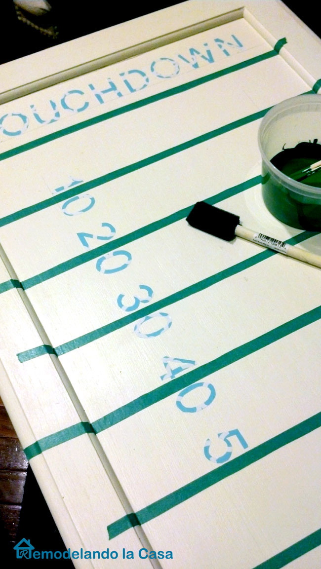 the lines, numbers and touchdown words are painted on a football field tray.